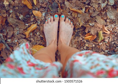 High angle view on naked feet of woman standing barefoot on the dry leaves in the woods nature park in autumn day unshod barefooted