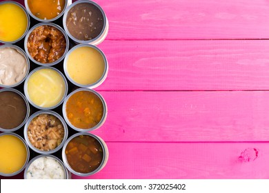 High Angle View of Open Cans of Soup in Wide Variety of Flavors on Bright Pink Painted Wooden Background with Ample Copy Space