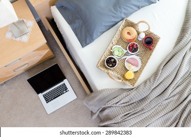 High Angle View of Open Laptop on Floor Beside Unmade Bed in Hotel Room with Wicker Breakfast Tray