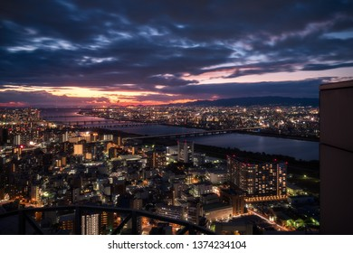 High angle View of Osaka City with bridges over Yodo River from the top of Umeda Sky Building with a magic sunset in the background in the  Kansai Region, Japan.