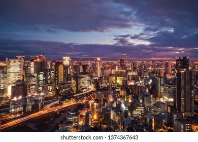 High angle view of Osaka City from the top of Umeda Sky Building in the evening with bright city lights and light trails in the  Kansai Region, Japan.