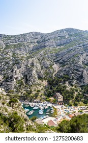 High angle view over the small fishing port in the steep-sided valley of the calanque de Morgiou on the mediterranean shore between Marseille and Cassis in the south of France on a sunny spring day.