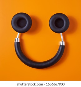 high angle view of a pair of black wireless full size headphones upside down on an orange background, resembling a smiley face