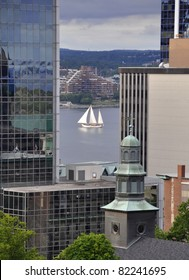 high angle view past the tall buildings of downtown Halifax towards the harbor, Tallship sailing by in between the buildings; Halifax Nova Scotia Canada