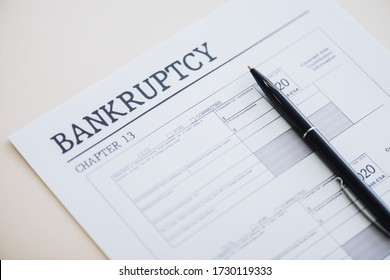 High angle view of pen on document with bankruptcy and chapter 13 lettering on white