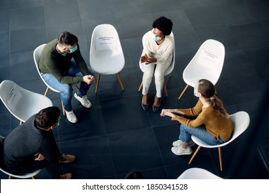 High angle view of people communicating while having group therapy during COVID-19 pandemic.