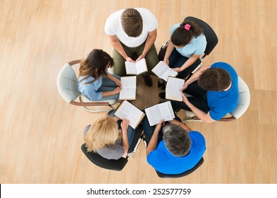 High Angle View Of People Reading Bible Together