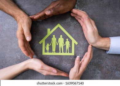 High Angle View Of Person Hands Protecting Family Home On Table