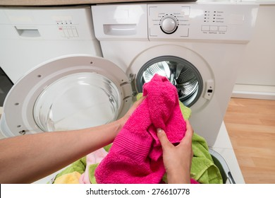 High Angle View Of Person Hands Putting Colorful Towels Into The Washing Machine
