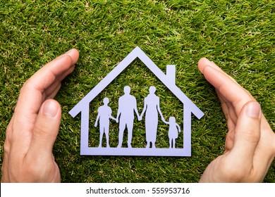 High Angle View Of Person Holding Protective Hand On Family Home At Grass
