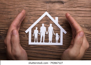High Angle View Of Person Holding Protective Hand On Family Home On Wooden Table