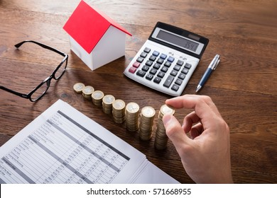 High Angle View Of A Person Stacking Coins Near House On Wooden Desk. Property Tax Concept
