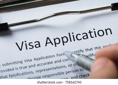 High Angle View Of Person's Finger With Pen Over Visa Application Form