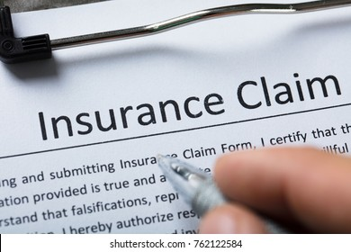 High Angle View Of Person's Finger Over Insurance Claim Form