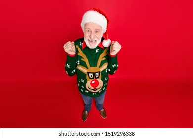 High angle view photo of santa looking on low x-mas shopping prices crazy shopper wear x-mas ugly ornament sweater hat and jeans isolated red background