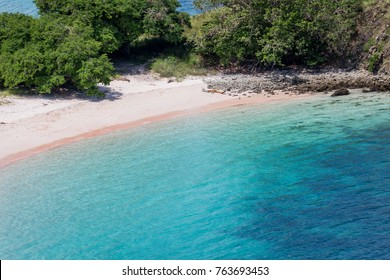 High angle view at Pink beach with turquoise water of Flores sea and tourist boat. The island is in Flores, Komodo islands, Indonesia.