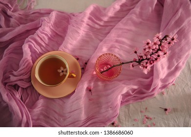High angle view of pink cup with tea, cherry blossom twig in pink glass and petals and flowers spread out on pink scarf.  Horizontal phot.o