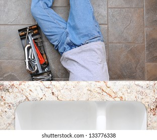 High angle view of a plumber laying under a kitchen sink. Man is unrecognizable with a tool box next to him.