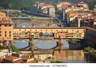 High angle view of Ponte Vecchio in Florence with three other bridges in the distance across the Arno river; Ponte Vecchio reflected in the tranquil water