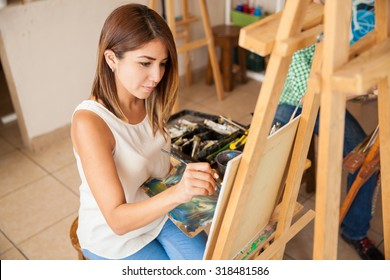 High angle view of a pretty brunette focused on a painting at her art school