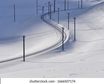 High angle view of railway tracks and power line by snow covered mountain pass