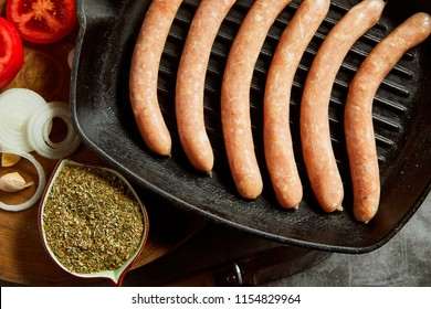 High angle view of raw pork sausages on grill pan with ingredients and spices