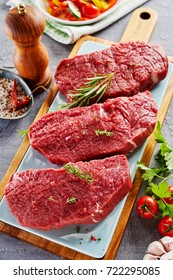 High angle view of raw rump steak cut in slices with spices prepared on wooden cutting board