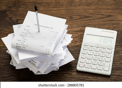 High Angle View Of Receipts With Calculator On Wooden Table