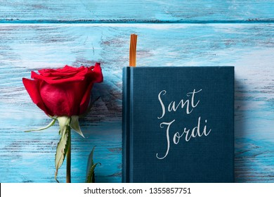 high angle view of a red rose and a book with the text Sant Jordi, the Catalan name for Saint George Day, when it is tradition to give red roses and books in Catalonia, Spain