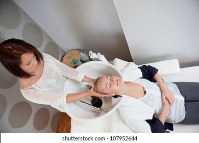 High angle view of relaxed young woman getting a head massage at a beauty salon