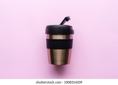 High angle view of reusable coffee cup on pink background
