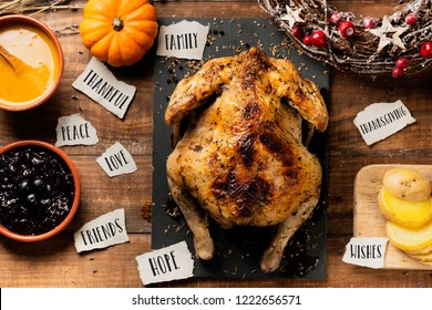 high angle view of a roast turkey on a wooden table next to some other food and some pieces of paper with words such as family, thankful, peace, love, friends, hope, thanksgiving or wishes