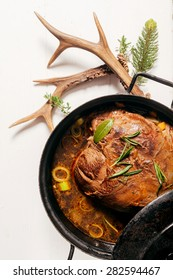 High Angle View of Roast Venison in Deep Pot with Fresh Herbs on White Wooden Surface Accented by Evergreen Sprigs and Deer Antlers