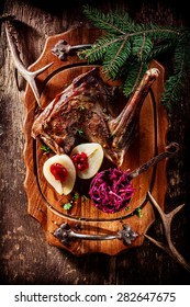 High Angle View of Roasted Venison Haunch on Wooden Tray with Prepared Pears on Rustic Table with Evergreen Sprigs and Deer Antlers