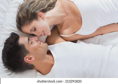 High angle view of romantic young couple lying in bed at home