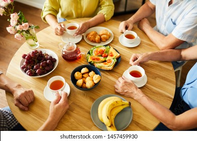 High angle view at round dinner table with unrecognizable senior people enjoying tea and deserts