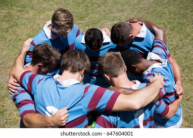 High angle view of rugby team making  huddle while standing at playing field on sunny day
