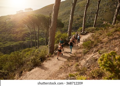 High angle view of running club group training on mountain trails. Group of fit athletes running on mountain path.