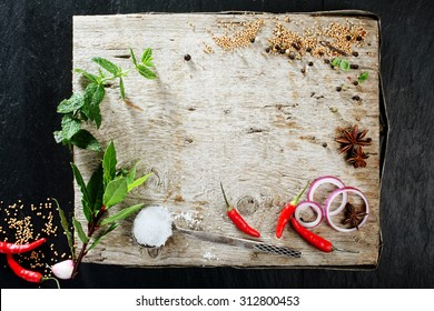High Angle View of Rustic Cutting Board with Various Fresh Herbs, Spices, and Peppers Scattered on its Surface with Copy Space