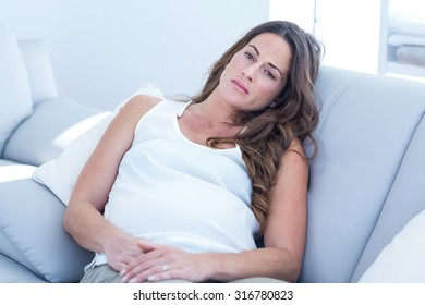 High angle view of sad pregnant woman leaning on sofa at home