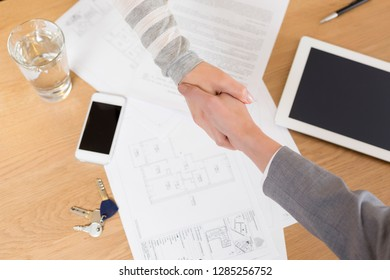 High angle view of saleswoman and client shaking hands over documents on table in apartment