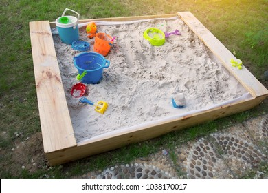 High angle view of a sand box in home garden plus some fork, and buckets