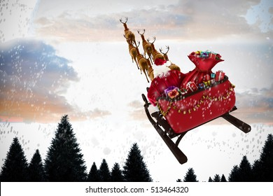 High angle view of Santa Claus riding on sled during Christmas against snow falling on fir tree forest