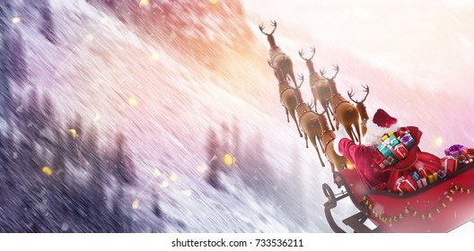 High angle view of Santa Claus riding on sled with gift box against snowy pine trees on alp mountain slope