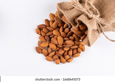 High angle view scattered almonds with sack on white background. vertical