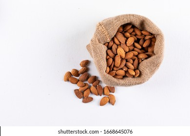 High angle view scattered almonds in sack on white background. horizontal