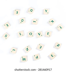 High Angle View of Scattered Wooden Scrabble Letter Tiles For Love Concept Isolated on White Background.
