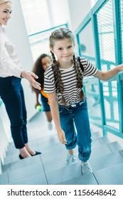 high angle view of schoolgirls going upstairs with teacher at school corridor