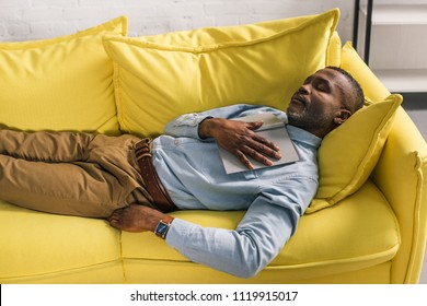 high angle view of senior african american man sleeping with book on sofa