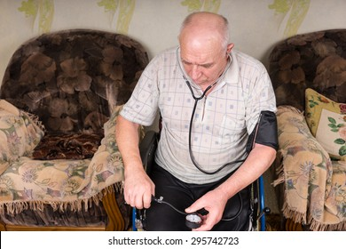 High Angle View of a Senior Bald Man Sitting on his Wheelchair, Checking his Blood Pressure Alone Using Apparatus in the Living Room.